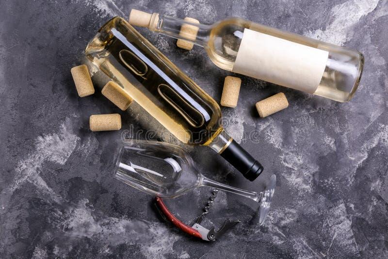 瓶白酒和拔塞螺旋在灰色背景 库存图片