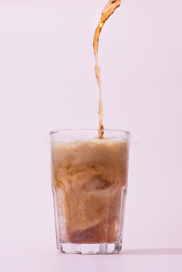 从瓶的倾吐的可乐到与飞溅的玻璃里 图库摄影