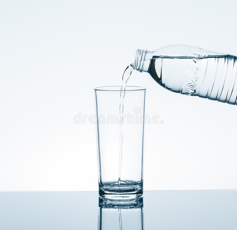 从瓶的倾吐的饮用水到在白色背景的水杯里 库存图片
