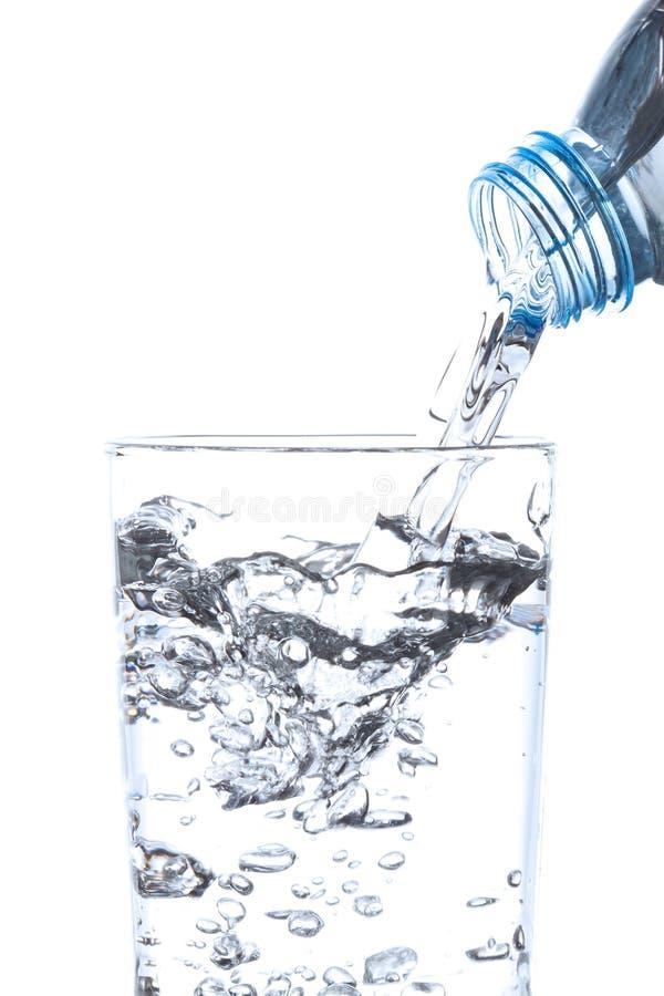 从瓶的倾吐的饮用水到玻璃里 免版税库存照片
