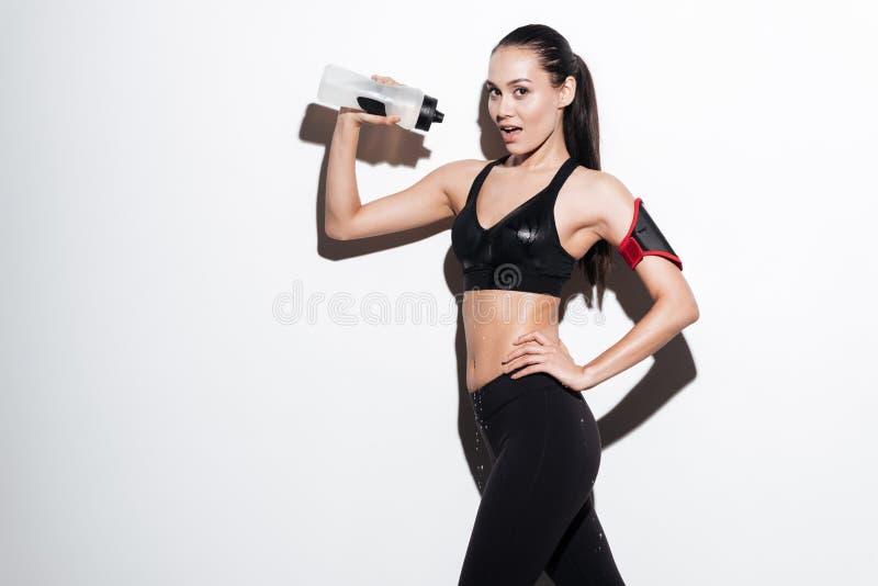 从瓶的愉快的引诱的女子运动员倾吐的水在她自己 图库摄影