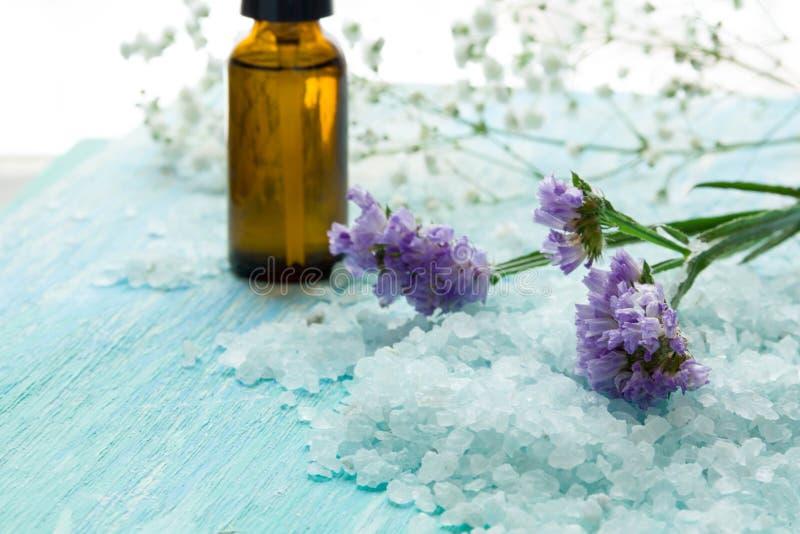 瓶精油和海盐在一张蓝色木桌上,温泉 免版税库存照片