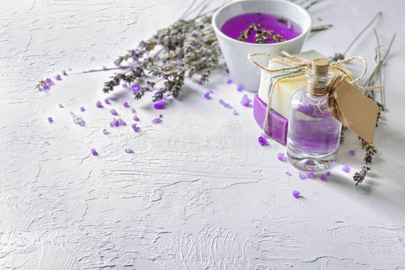 瓶精油用淡紫色和肥皂在轻的桌上 图库摄影