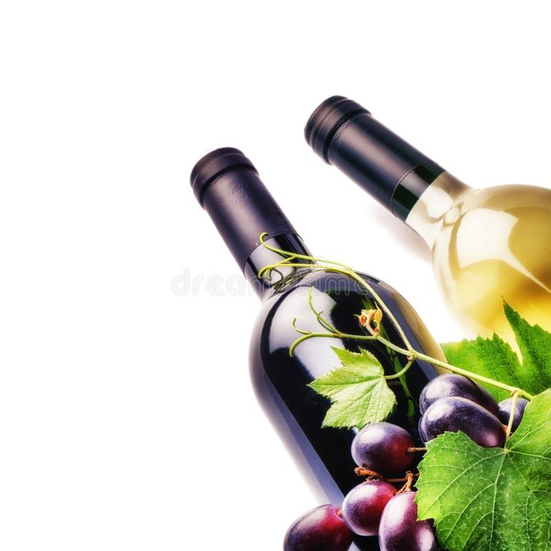 瓶红色和白葡萄酒用新鲜的葡萄 免版税库存照片