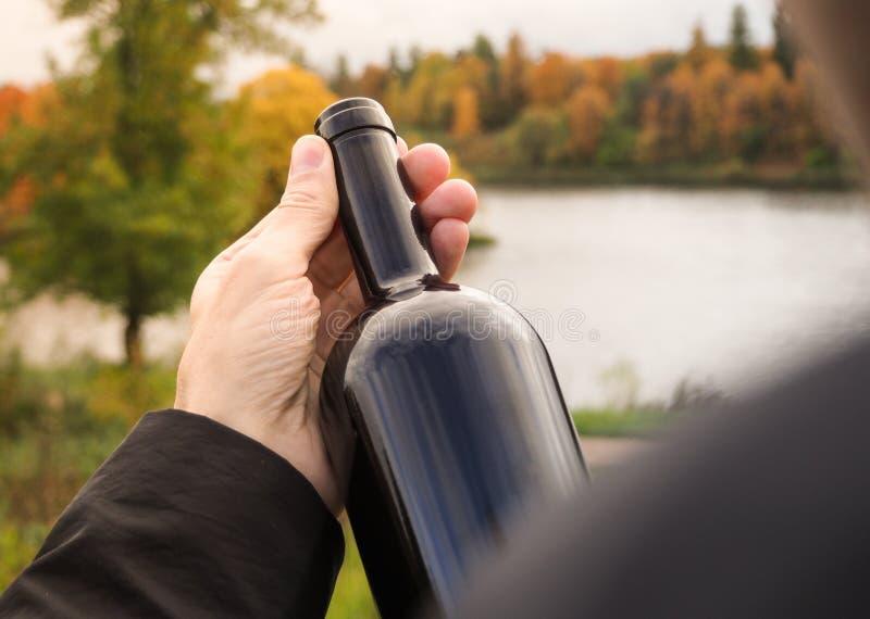 瓶红葡萄酒在一个人的手上一个黑斗篷的 免版税库存图片