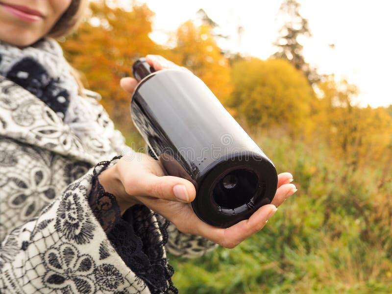 瓶红葡萄酒在女性手上在一座老城堡的背景 免版税图库摄影