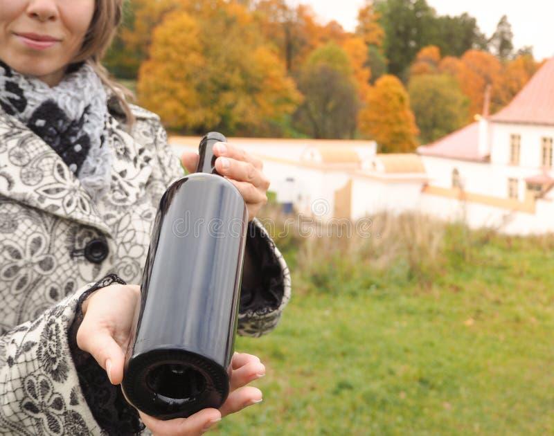 瓶红葡萄酒在女性手上在一座老城堡的背景 免版税库存照片
