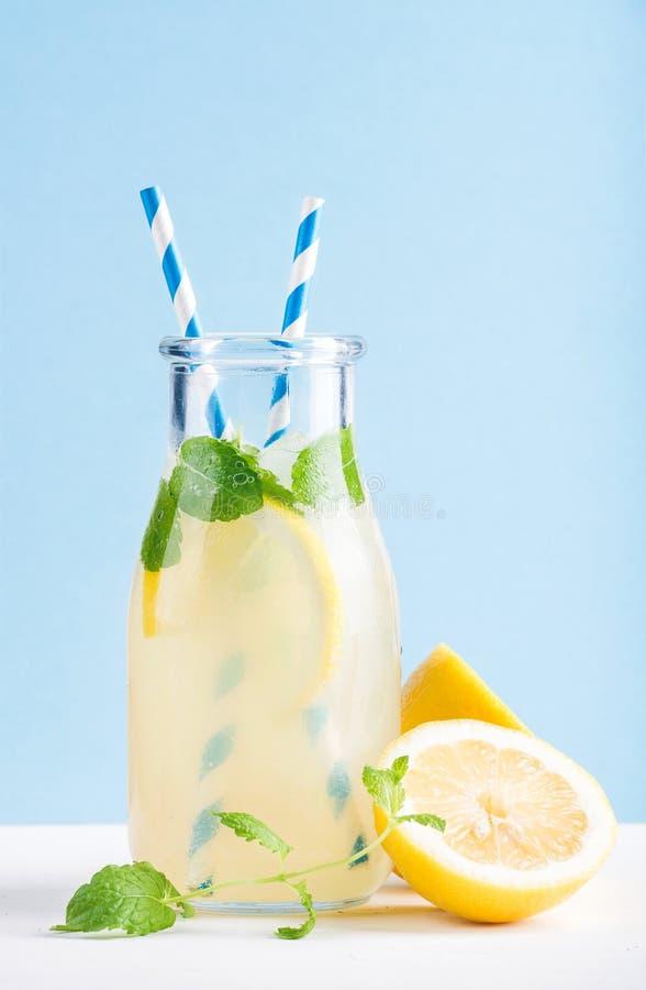 瓶自创柠檬水用薄菏、冰、柠檬、纸秸杆和淡色蓝色背景 库存照片
