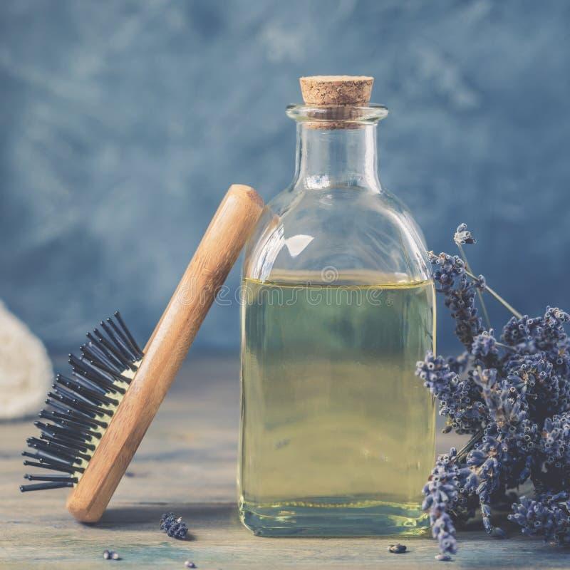 瓶自然化妆熏衣草油,头发和身体治疗、棉花毛巾和木按摩梳子 免版税图库摄影