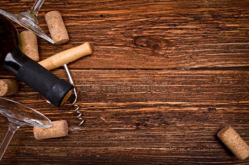 瓶酒、拔塞螺旋和黄柏在木桌上 背景 免版税图库摄影