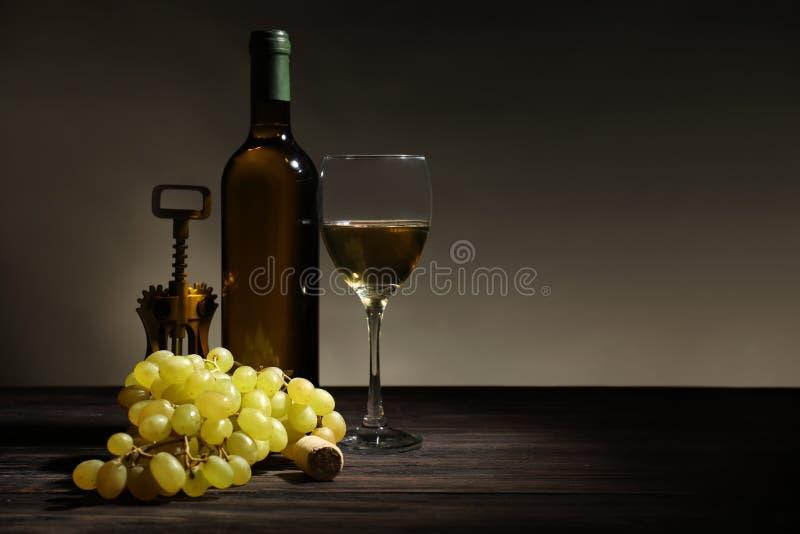 瓶酒、玻璃和拔塞螺旋在黑暗的背景 免版税图库摄影