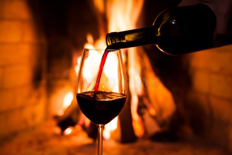 瓶酒和一块玻璃反对火 免版税库存图片