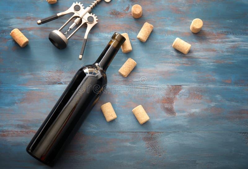 瓶酒和拔塞螺旋在木桌上 免版税库存照片
