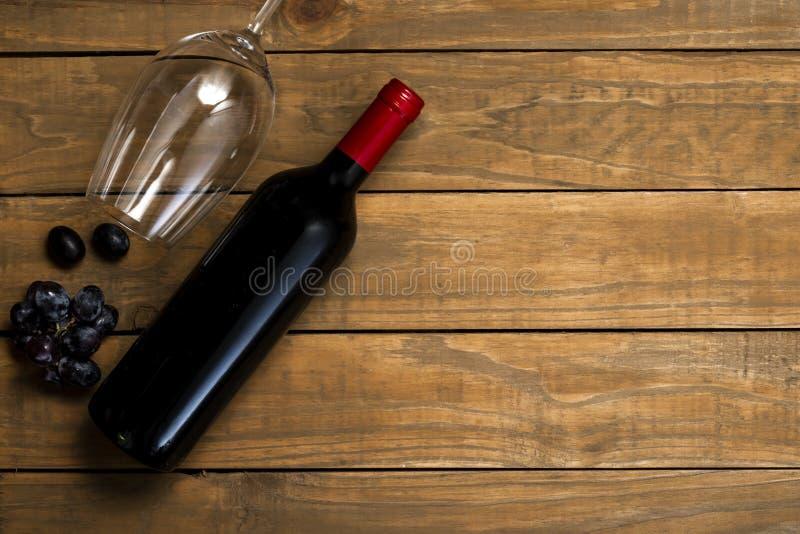 瓶酒和玻璃和葡萄在木背景 与拷贝空间的顶视图 免版税图库摄影