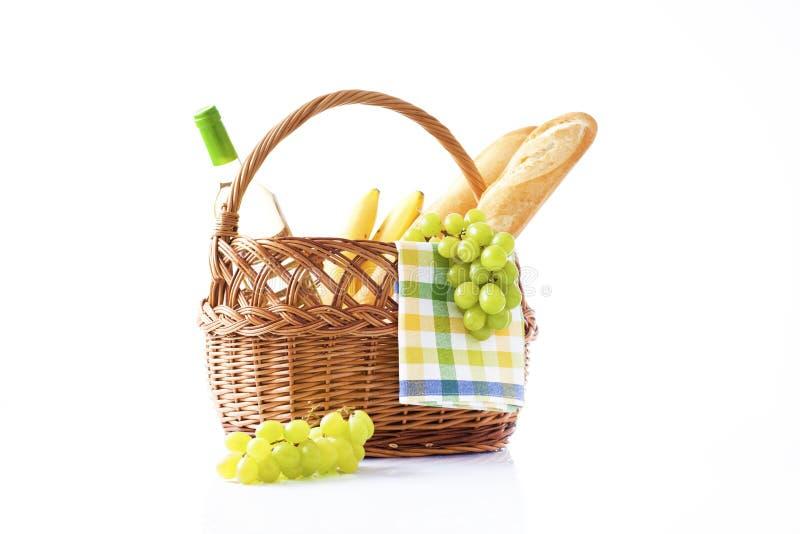 瓶酒和野餐篮子用可口食物 免版税图库摄影