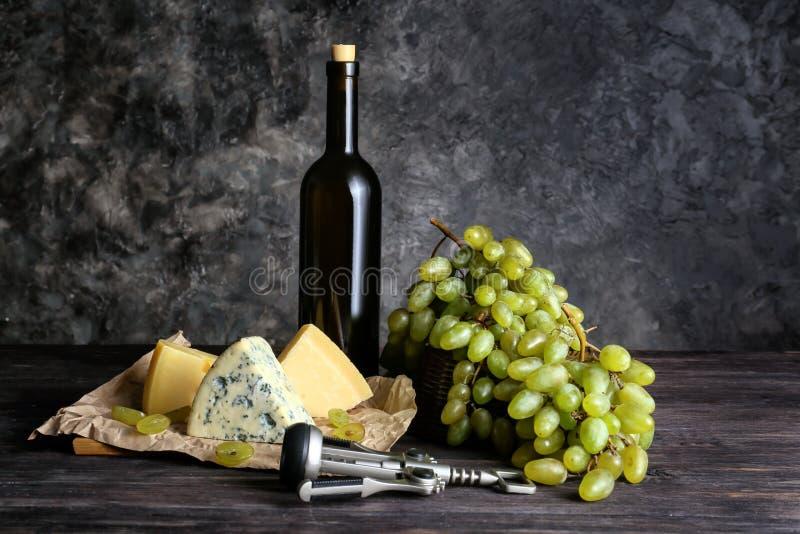 瓶酒用乳酪和成熟葡萄在木桌上 免版税图库摄影