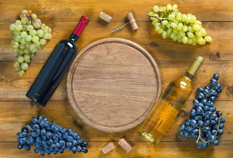 瓶酒,葡萄和圆的切板顶视图  图库摄影