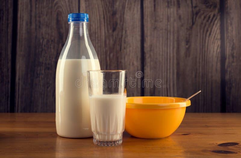 瓶静物画牛奶、杯牛奶和黄色塑料碗 免版税库存图片