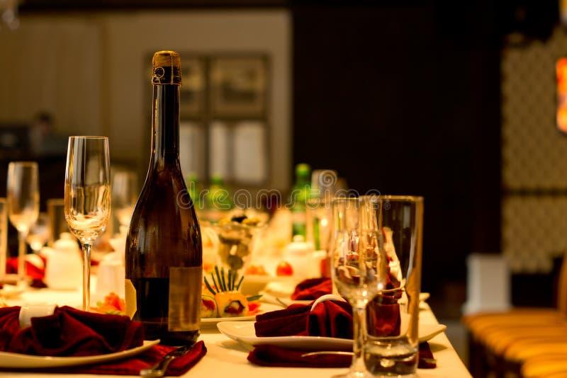 瓶香槟和长笛在一张正式桌上 免版税库存图片