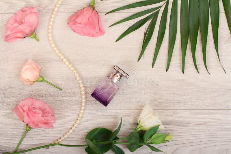 瓶香水,在串的小珠与白色和桃红色花和绿色叶子在木背景 Woomen化妆用品 免版税库存图片