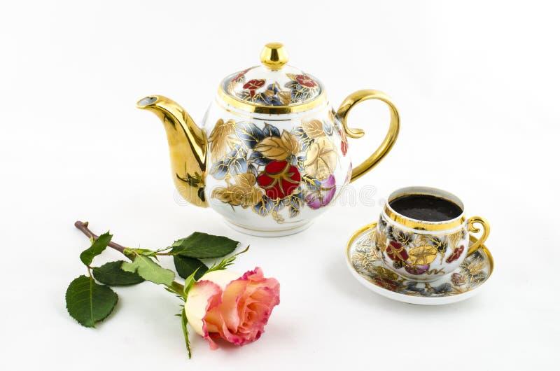 瓷咖啡具(杯子和水罐)与玫瑰色花 免版税库存照片