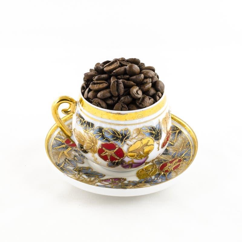 瓷咖啡杯用在白色隔绝的咖啡豆填装了 库存照片
