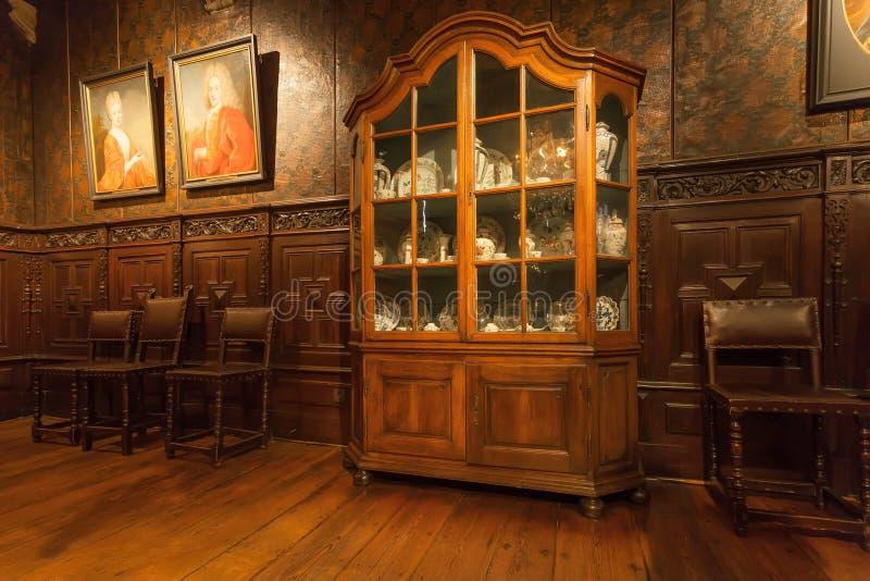 瓷在古色古香的碗柜架子设置了在Plantin-Moretus打印博物馆,联合国科教文组织世界遗产名录站点 免版税库存图片