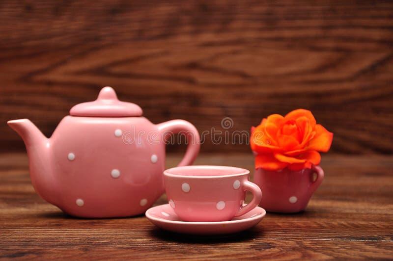瓷察觉了茶杯和水壶和橙色玫瑰 免版税库存图片