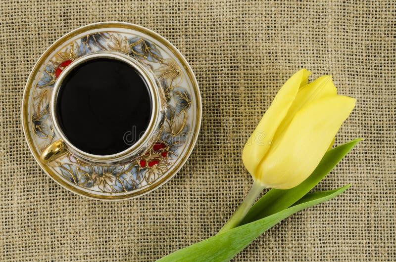 瓷有黄色花的咖啡杯在亚麻制背景 免版税库存照片