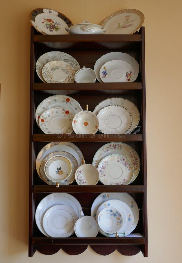 瓷盘、杯子和板材,在一个棕色桃花心木木架子的老汇集杯子 免版税图库摄影
