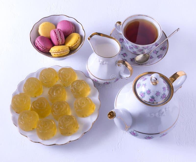 瓷茶具用牛奶、通心面和橘子果酱、牛奶罐、茶杯、茶杯,胶粘的糖果 免版税图库摄影