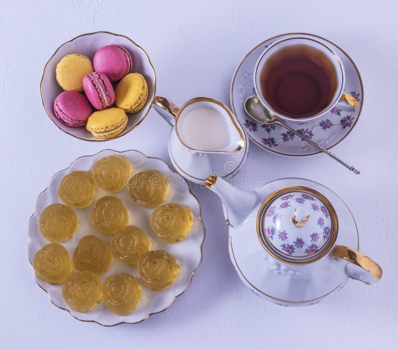 瓷茶具用牛奶、通心面和橘子果酱、牛奶罐、茶杯、茶杯,胶粘的糖果 免版税库存照片