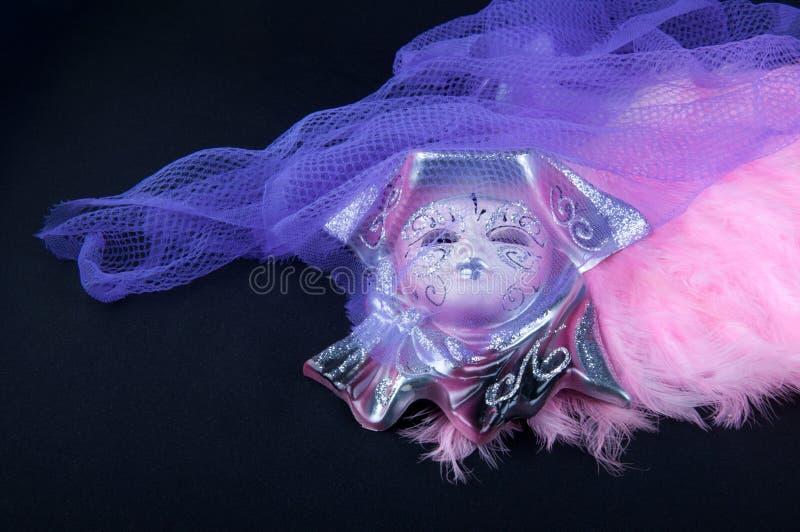 天色网_瓷面具在黑背景放置在紫罗兰色网和桃红色羽毛附近