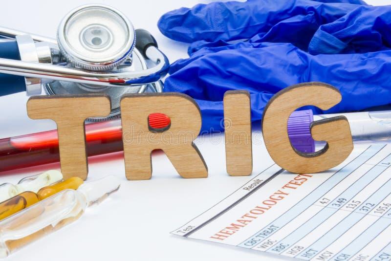 甘油三酸酯的TRIG实验室医疗简称测试概念照片 在桌上是实验室首字母缩略词TRIG在blo旁边管  免版税库存照片