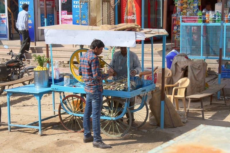 甘蔗汁液的卖主在新闻和买家附近的 免版税库存照片