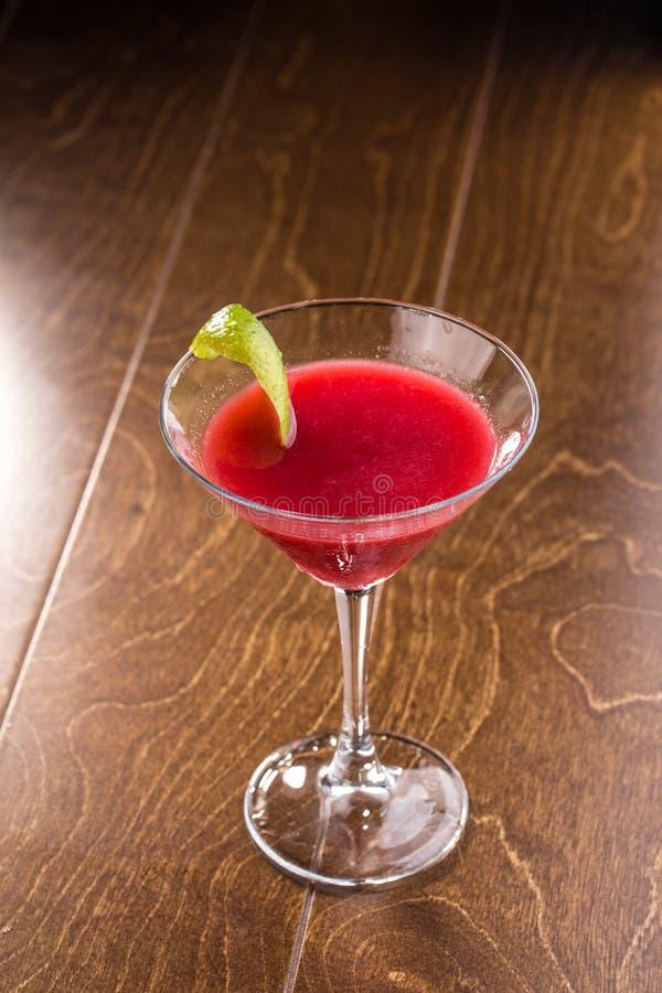 甜与石灰果皮的夏天草莓酒精鸡尾酒在木桌上的马蒂尼鸡尾酒玻璃 图库摄影