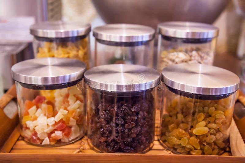 甜五颜六色的玻璃杯子、瓶子或者瓶在显示在木盘子在厨房或餐具室顶部的结冻,无核小葡萄干,苏丹娜, 免版税图库摄影