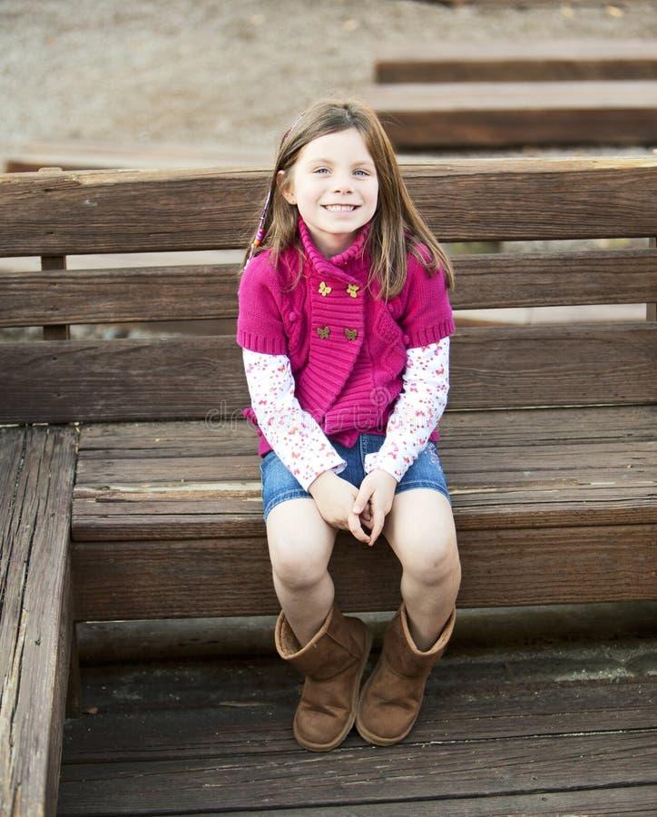 甜俏丽的女孩坐长凳 免版税库存照片