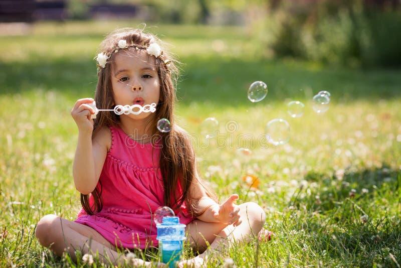 甜可爱的小女孩吹的肥皂bubb美丽的画象  图库摄影