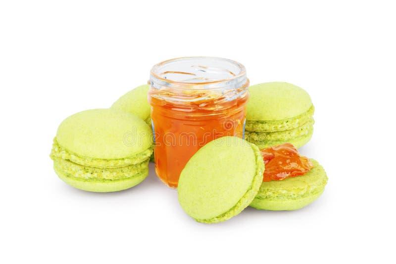 甜和五颜六色的法国蛋白杏仁饼干或macaron与一个瓶子果酱在白色背景 免版税库存图片