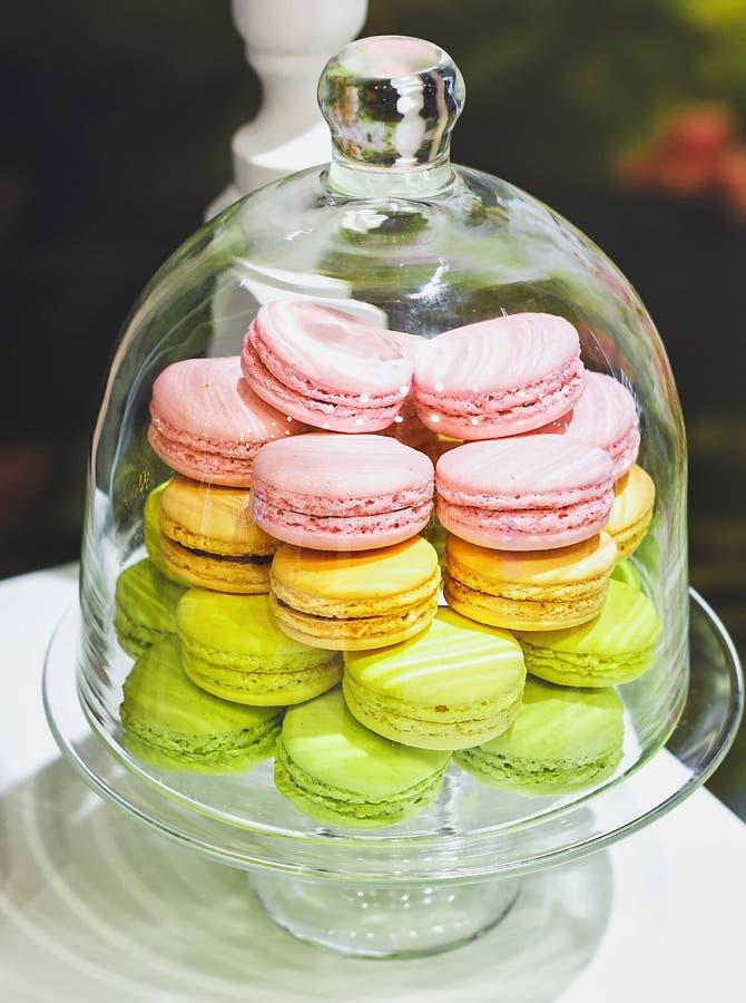 甜和五颜六色的法国蛋白杏仁饼干或macaron在玻璃钟形玻璃容器或玻璃盘子在一张白色木桌上 点心 可以是半新fo 免版税库存图片