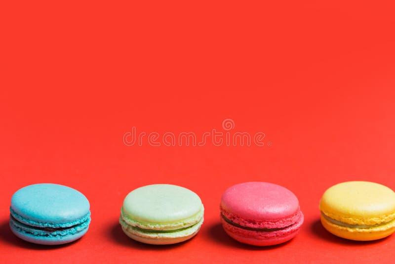 甜和五颜六色的法国蛋白杏仁饼干或macaron在红色背景 点心,自创蛋糕 免版税库存照片
