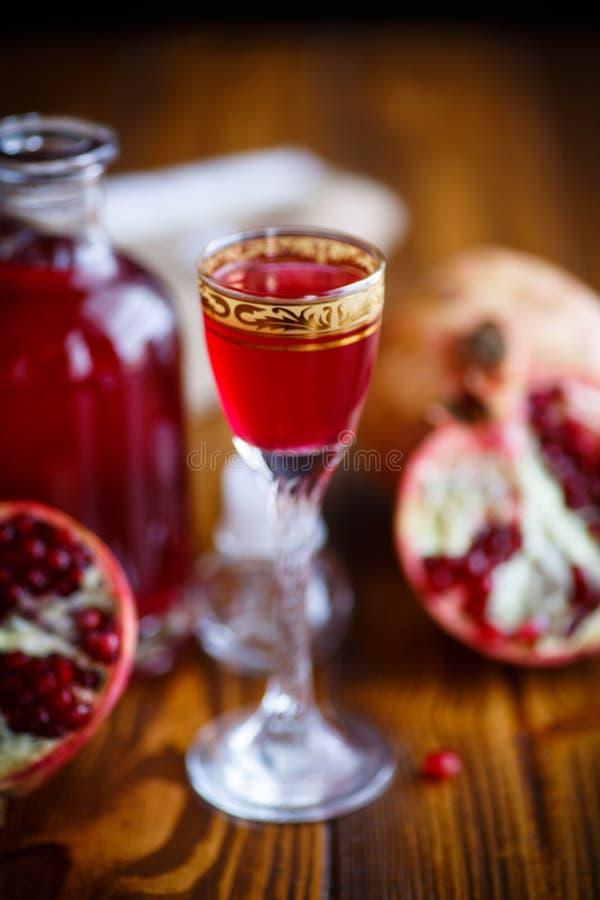 甜在蒸馏瓶的石榴酒精甘露酒有玻璃的 库存照片