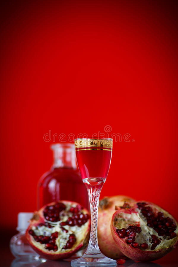 甜在蒸馏瓶的石榴酒精甘露酒有玻璃的 免版税图库摄影