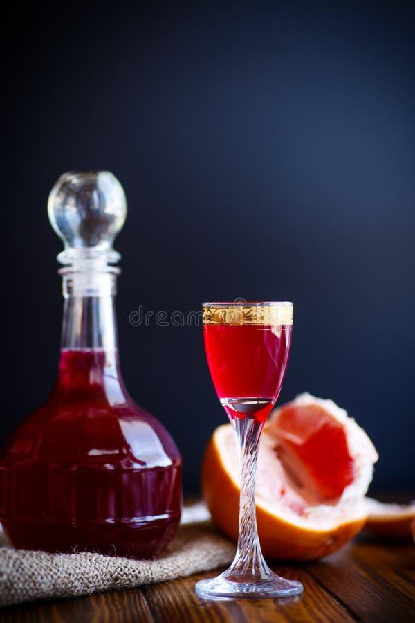 甜在蒸馏瓶的葡萄柚酒精甘露酒有玻璃的 免版税库存图片