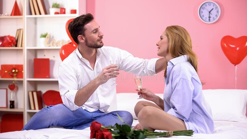 甜夫妇挥动的和饮用的香槟在床上,庆祝情人节 图库摄影
