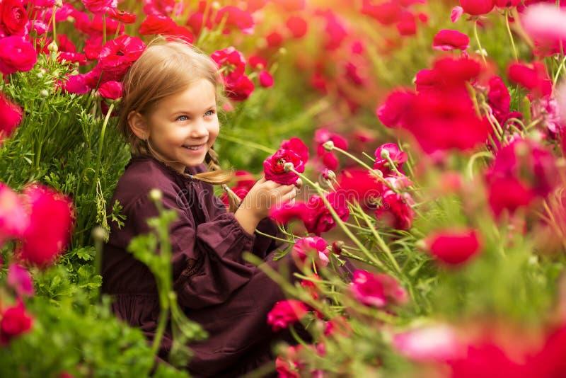 甜女孩在有狂放的春天花的一个草甸 库存照片