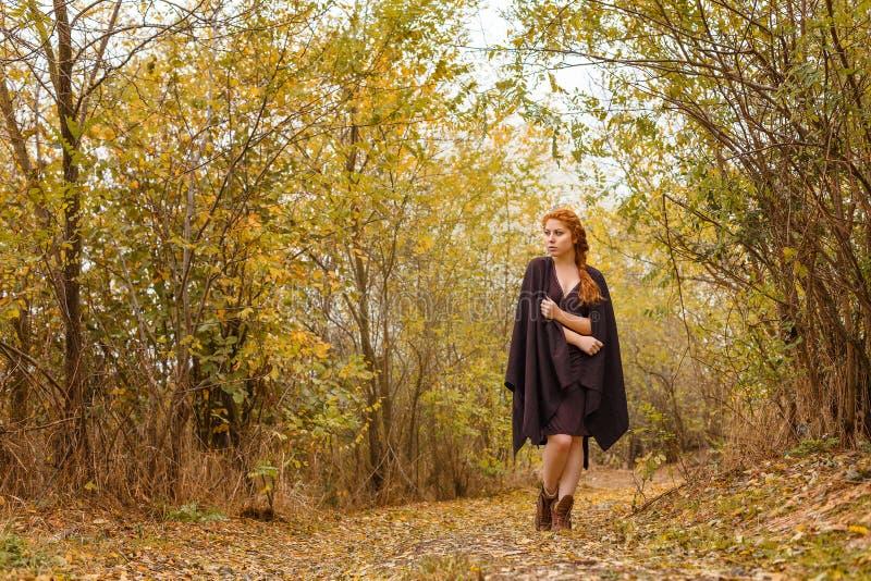 甜女孩在秋天森林、寂寞和忧郁里 免版税库存图片