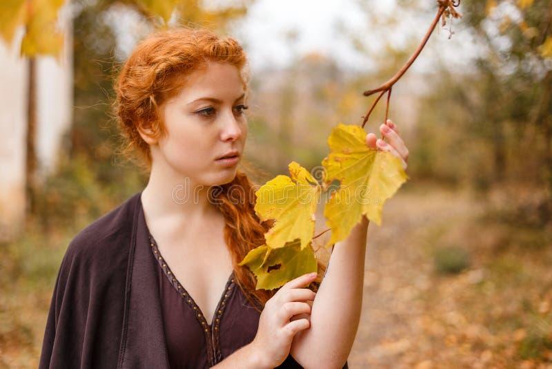甜女孩在秋天森林、寂寞和忧郁里 库存图片