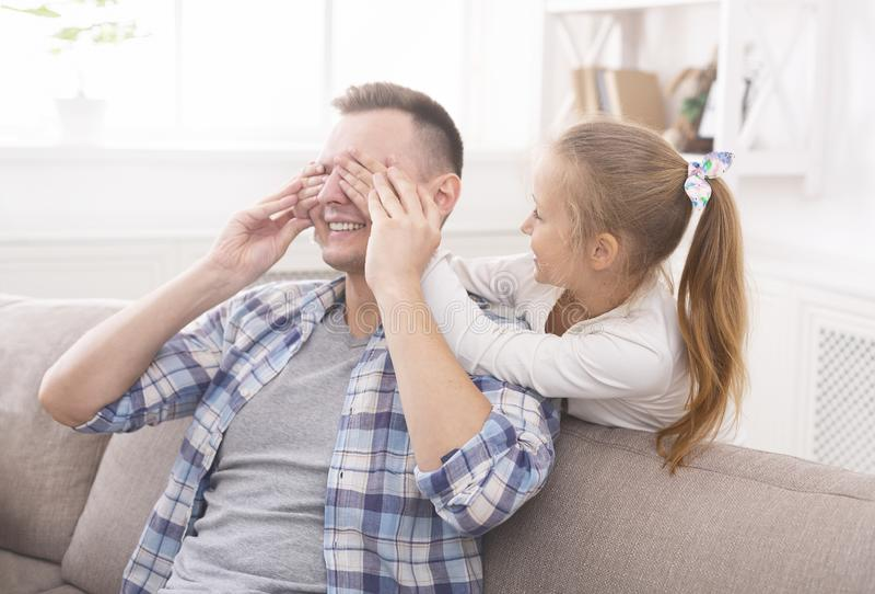 甜女孩闭上她的爸爸眼睛 免版税库存照片